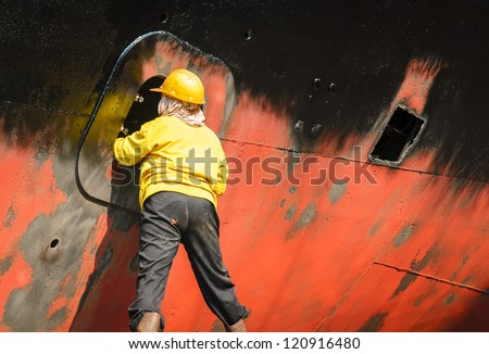 Worker cleaning side of ship at shipyard - stock photo