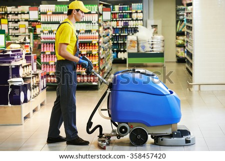 worker cleaning store floor with machine - stock photo
