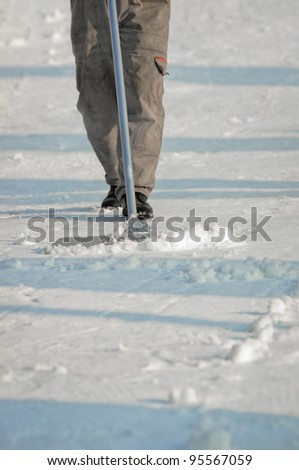 Worker cleaning the streets covered by snow - stock photo