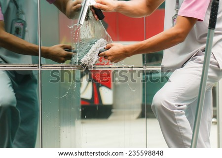 Worker cleaning windows in building-2 - stock photo