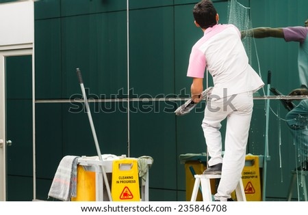 Worker cleaning windows in building