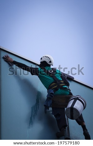 worker cleaning windows service on high rise building - stock photo