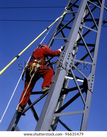 Worker climbing to fix the electric line - stock photo