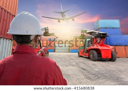Worker control Containers with forklift at yard ,beautiful sky at dusk with plane background