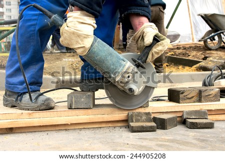 worker cuts the stone, side view. - stock photo
