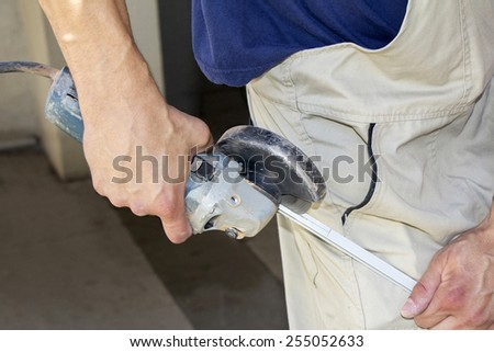 Worker cutting aluminum with angle grinder in workshop