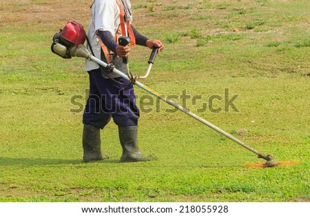 Worker cutting grass in garden with the weed trimmer - stock photo