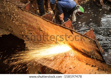 Worker cutting metal and sparks spread