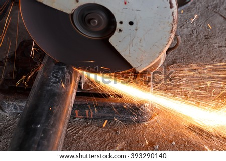 Worker cutting metal. Sparks while grinding iron.