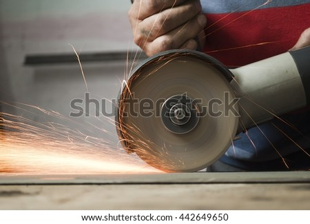 Worker cutting metal Sparks while grinding iron - stock photo