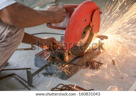 Worker cutting metal with cutter for house construction