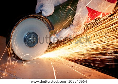 Worker cutting metal with grinder. - stock photo