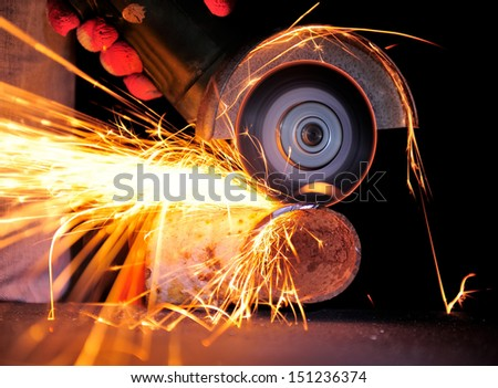 bench grinder sparks. worker cutting metal with grinder. sparks while grinding iron bench grinder
