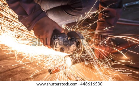worker cutting metal with grinder. Sparks while grinding iron. - stock photo