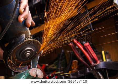 Worker cutting metal with grinder. Sparks while grinding iron. Selective low focus  - stock photo