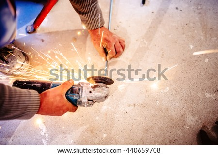 worker cutting steel bars using manual grinder - stock photo