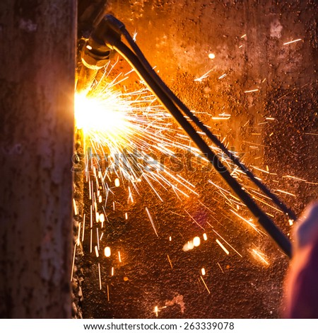 worker cutting steel board using metal torch - stock photo
