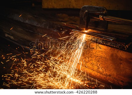 Worker cutting steel with acetylene welding cutting torch. - stock photo