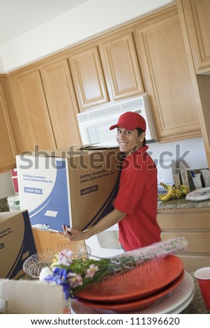 Worker delivering cardboard boxes into new house - stock photo