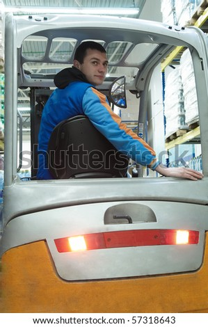 Worker driver of a forklift loader at food warehouse distribution works - stock photo