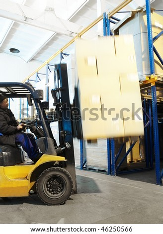 Worker driver of a forklift loader at warehouse loading cardboard boxes on pallet - stock photo