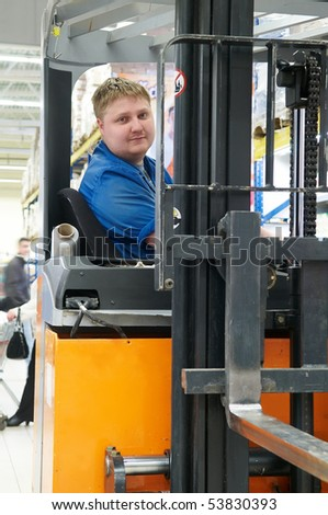 Worker driver of a forklift loader in blue workwear at warehouse