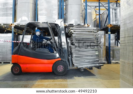 Worker driver of a forklift loader in blue workwear at warehouse moving wooden pallets