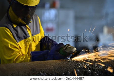 Worker during use electric wheel grinding on steel structure in factory work shop.