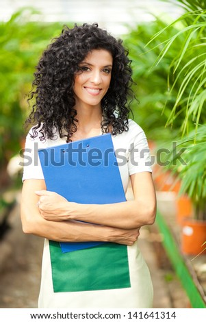 Worker examining plants in a greenhouse  - stock photo
