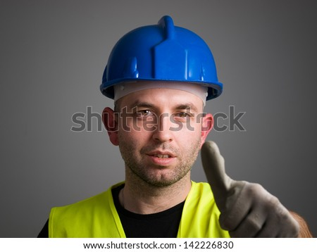 Worker expressing positivity with ok symbol. The worker is isolated on dark background. - stock photo