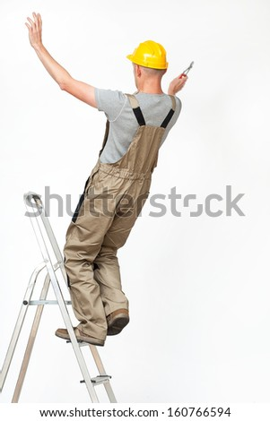Worker falling from ladder while working at height - stock photo