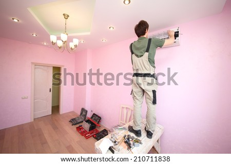 Worker fastens grid of air conditioning in the new modern apartment - stock photo
