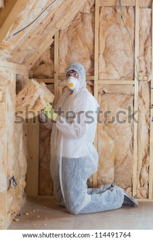 Worker filling walls with insulation in construction site - stock photo