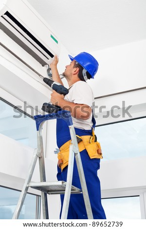 Worker finished mounting air conditioning indoor unit - stock photo
