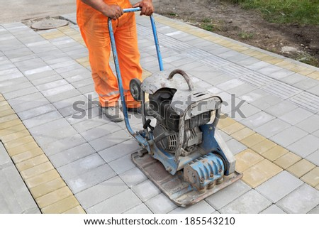 Worker finishing concrete brick pavement with vibratory plate compactor - stock photo