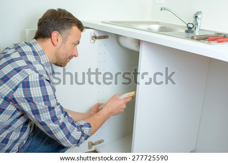 Worker fitting a kitchen - stock photo