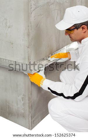 Worker fixing a lath on a corner - stock photo