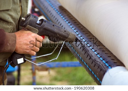 Worker fixing filter paper on perforated pipe with hot plastic glue gun - stock photo