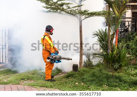 Worker fogging residential area with insecticides to kill aedes mosquito breeding ground, carrier of dengue virus - stock photo
