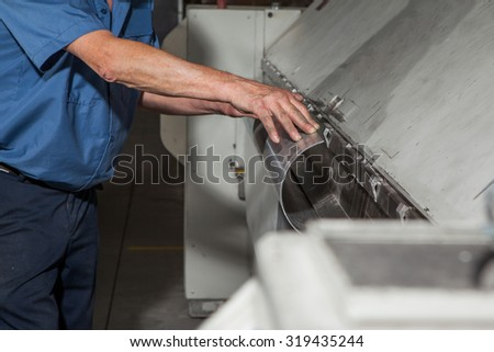 worker folding metal at the factory - stock photo