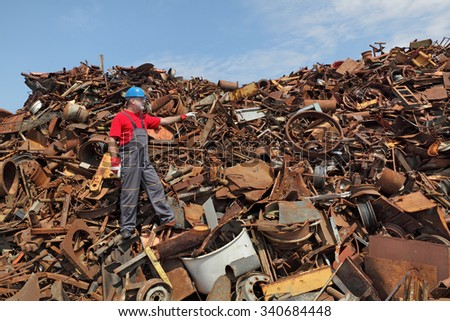 Worker gesturing at heap of scrap metal ready for recycling, pointing