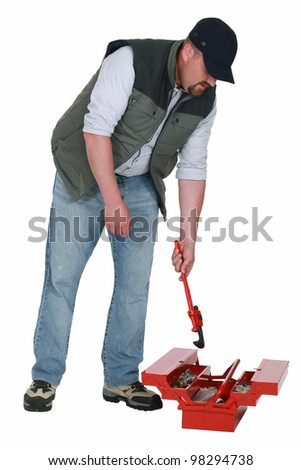 Worker getting a wrench out of a toolbox - stock photo