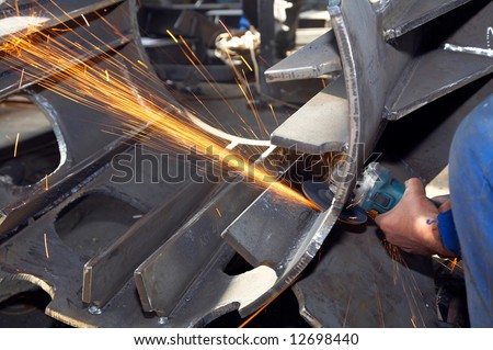 worker grinding a metal piece and sparks spreading