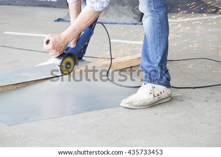 Worker grinding a metal plate in the street.