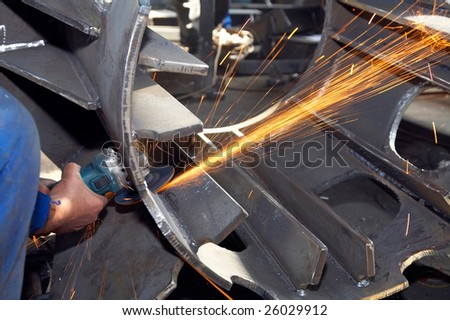 worker grinding metal and sparks spreading