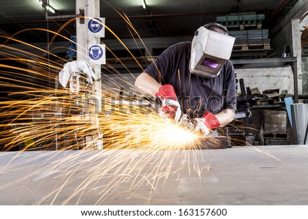 Worker Grinding metal in a workshop with sparks flying - stock photo