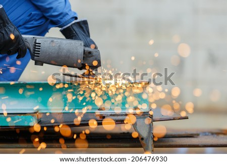 worker grinding steel by electric grinding machine - stock photo