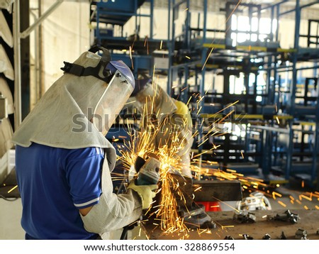 Worker grinding steel in work shop for maintenance in factory