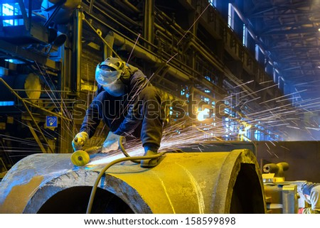 Worker handles metal product Foundry - stock photo