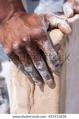 Worker - hands covered with clay. Construction.